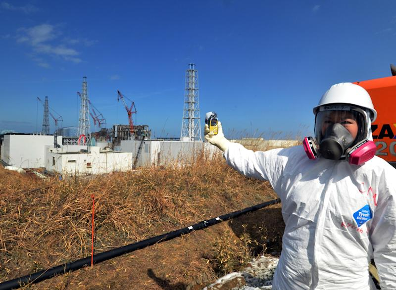 A journalist checks radiation level with her dosimeter near stricken Fukushima Dai-ichi nuclear power plant of Tokyo Electric Power Co., during a press tour led by TEPCO officials, in Okuma town, Fukushima prefecture, northeastern Japan Tuesday, Feb. 28, 2012. Japan next month marks one year since the March 11 tsunami and earthquake, which triggered the worst nuclear accident since Chernobyl in 1986.  (AP Photo/Yoshikazu Tsuno, Pool)