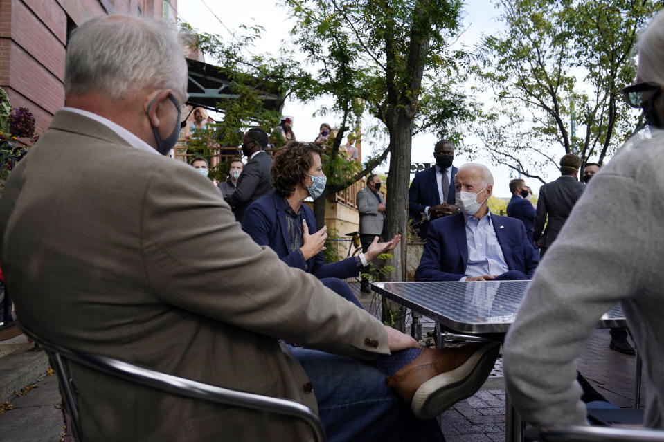 Democratic presidential candidate former Vice President Joe Biden talks to Mayor of Duluth Emily Larson, second from left, and Minnesota Gov. Tim Walz, at the Amazing Grace Bakery & Cafe in Duluth, Minn., Friday, Sept. 18, 2020. (AP Photo/Carolyn Kaster)
