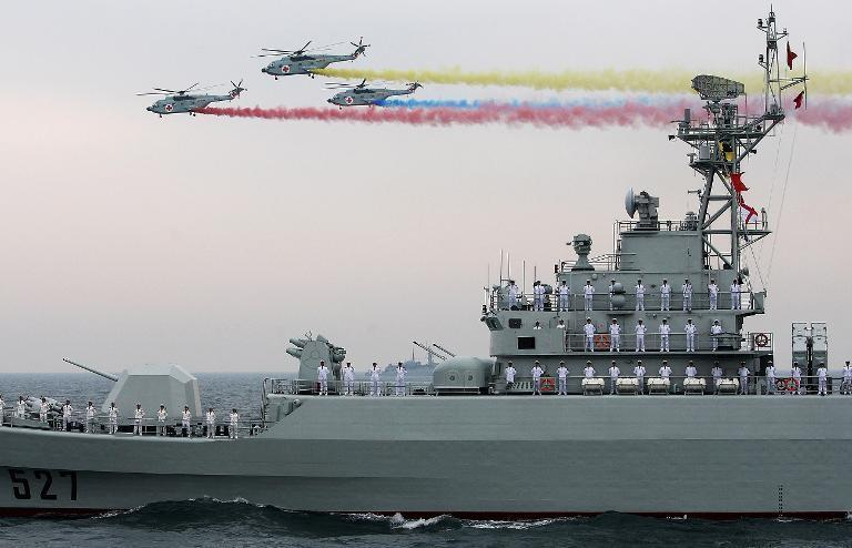 Chinese Navy helicopters fly over a People's Liberation Army Navy warship on April 23, 2009 off Qingdao in Shandong Province