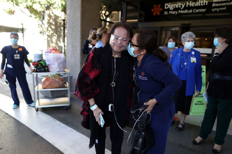 Intensive Care Unit Nurse Merlin Pambuan, is hugged by hospital staff as she walks out of the hospital where she spent 8 months with the coronavirus disease in Long Beach