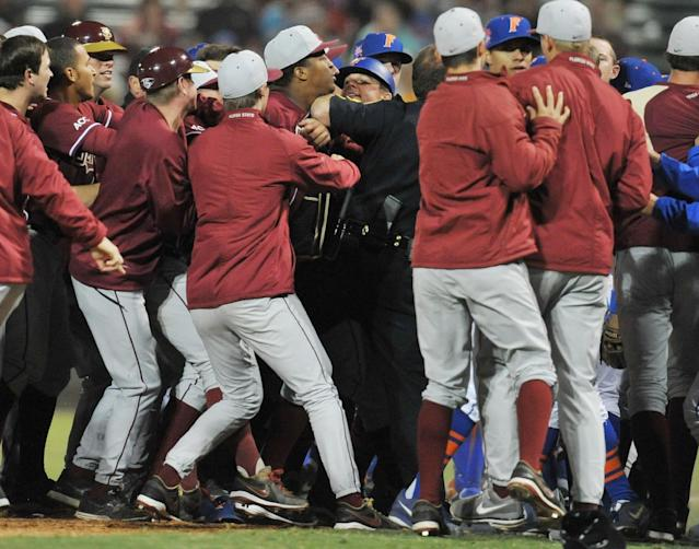 Florida State's Jameis Winston, center left, is held back by a sheriff's officer as Florida State and Florida players scuffle in the eighth inning of an NCAA college baseball game Tuesday, March 25, 2014, in Jacksonville, Fla. (AP Photo/The Florida Times-Union, Bob Self)