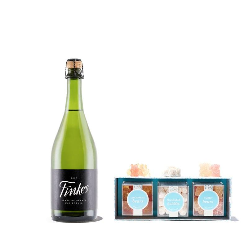 """<p><a href=""""https://www.popsugar.com/buy/Bubbly-Celebration-Set-499911?p_name=A%20Bubbly%20Celebration%20Set&retailer=winc.com&pid=499911&price=50&evar1=savvy%3Aus&evar9=42473080&evar98=https%3A%2F%2Fwww.popsugar.com%2Fsmart-living%2Fphoto-gallery%2F42473080%2Fimage%2F46745660%2FBubbly-Celebration-Set&list1=gift%20guide&prop13=mobile&pdata=1"""" rel=""""nofollow"""" data-shoppable-link=""""1"""" target=""""_blank"""" class=""""ga-track"""" data-ga-category=""""Related"""" data-ga-label=""""https://www.winc.com/gifts/gift-boxes/a-bubbly-celebration-12121"""" data-ga-action=""""In-Line Links"""">A Bubbly Celebration Set</a> ($50) boasts three boxes of Champagne-flavored candies and one bubbly bottle of booze.</p>"""