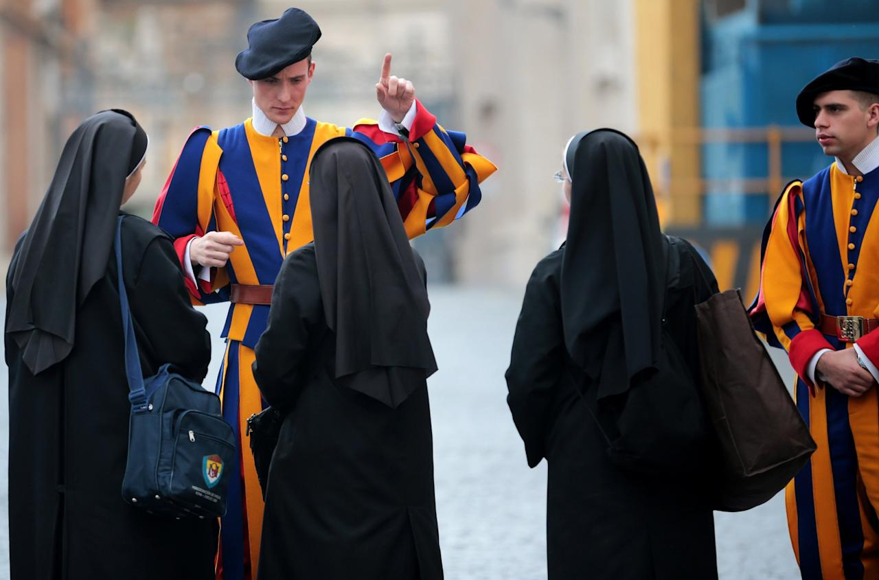 VATICAN CITY, VATICAN - FEBRUARY 26:  A member of the Pope's Swiss Guard gives directions to three nuns at the gates to St Paul's Basilica on February 26, 2013 in Rome, Italy. The Pontiff will hold his last weekly public audience on February 27, 2013 before he retires the following day. Pope Benedict XVI has been the leader of the Catholic Church for eight years and is the first Pope to retire since 1415. He cites ailing health as his reason for retirement and will spend the rest of his life in solitude away from public engagements.  (Photo by Christopher Furlong/Getty Images)