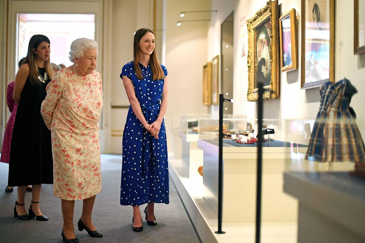 <p>Lucy Peter, the assistant curator of the exhibition accompanies the Queen as she looks at a dress worn by the future King Edward VII.</p>