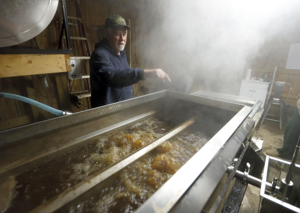 Keith Moore watches over some of the boiling sap he uses to make maple syrup on his Lawrence County Savage Farms on Feb. 14, 2018 in Louisa, Ky. (Charles Bertram/Lexington Herald-Leader via AP)