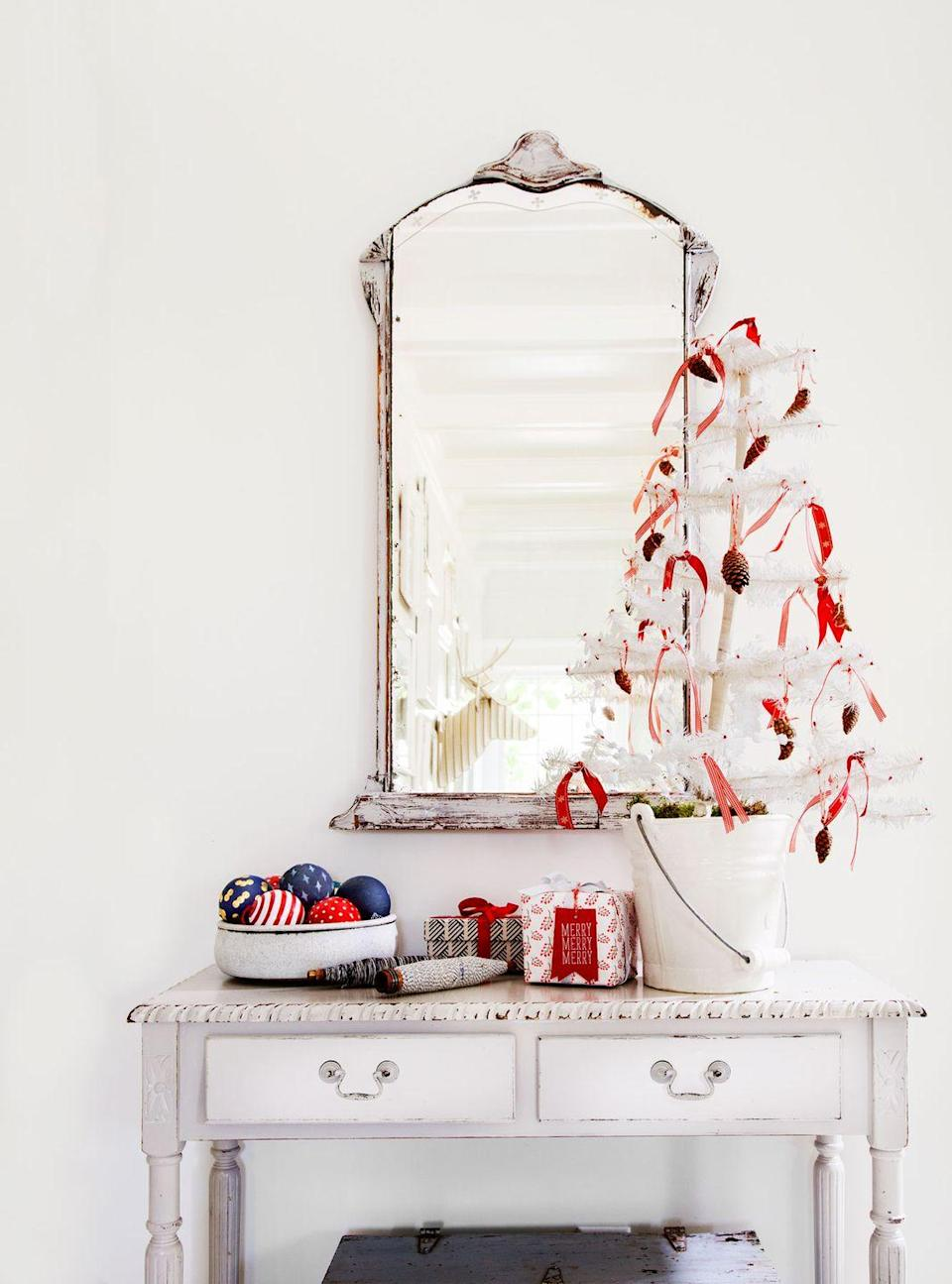 """<p>A petite <a href=""""https://www.countryliving.com/home-design/news/a45994/white-christmas-tree-decorating-ideas/"""" rel=""""nofollow noopener"""" target=""""_blank"""" data-ylk=""""slk:white tree"""" class=""""link rapid-noclick-resp"""">white tree</a> covered in red ribbons and pinecones makes for a simple but merry welcome in this entryway. </p><p><a class=""""link rapid-noclick-resp"""" href=""""https://www.amazon.com/Small-Artificial-Christmas-Tree-Pre-lit/dp/B077LHZFFS/?tag=syn-yahoo-20&ascsubtag=%5Bartid%7C10050.g.1247%5Bsrc%7Cyahoo-us"""" rel=""""nofollow noopener"""" target=""""_blank"""" data-ylk=""""slk:SHOP WHITE TREES"""">SHOP WHITE TREES</a></p>"""