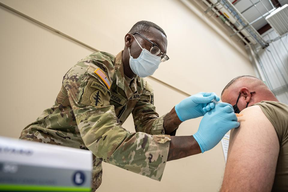 Preventative Medicine Services NCOIC Sergeant First Class Demetrius Roberson administers a COVID-19 vaccine to a soldier on September 9, 2021 in Fort Knox, Kentucky. (Jon Cherry/Getty Images)
