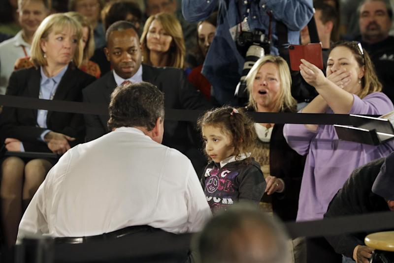 """People react as three-year-old Nicole Mariano tells New Jersey Gov. Chris Christie, """"my house is still broken,"""" during a town hall meeting Thursday, Feb. 20, 2014, in Middletown, N.J. Christie called her closer and promised that someone from his administration would see about helping her mom. Then they high-fived. Christie is blaming the federal government for deficiencies in the state's Superstorm Sandy recovery. (AP Photo/Mel Evans)"""