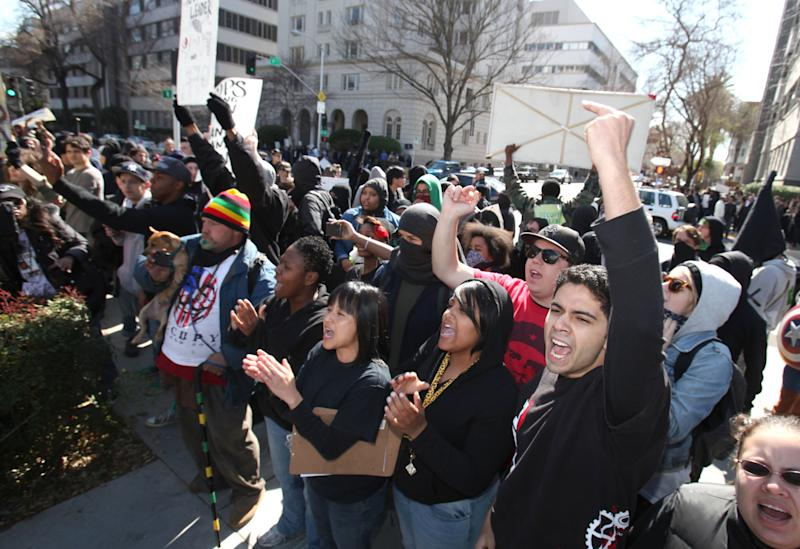 Members of the Occupy movement shout at a pro-white group as it holds a demonstration at  the Capitol in Sacramento, Calif., Monday, Feb. 27, 2012. A clash erupted later as California Highway Patrol and Sacramento city police officers escorted members of the group called the South Africa Project to a parking garage following their protest. Occupy members began throwing objects at the pro-white group. Two CHP officers were injured as they broke up the crowd.  Four protesters were arrested.(AP Photo/Rich Pedroncelli)