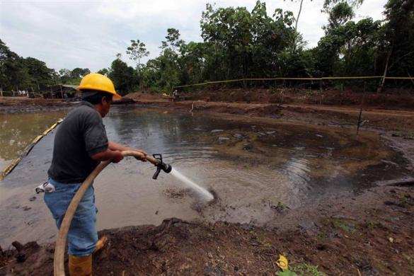 Ecuadorean workers clean up an oil waste pit owned by state petroleum company Petroecuador in Shushufindi, some 410 km (254 mi) east of Quito December 8, 2009.