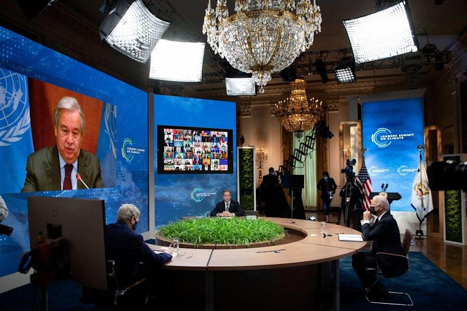 (From L-R) Climate envoy John Kerry, Secretary of State Antony Blinken, and President Biden listen as UN Secretary General Antonio Guterres speaks on screen during the climate summit from the East Room of the White House on 22 April (AFP via Getty Images)