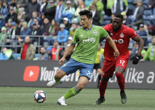 FILE - In this Saturday, April 13, 2019 file photo, Seattle Sounders midfielder Kim Kee-Hee, left, kicks the ball away from Toronto FC forward Jozy Altidore (17) during the first half of an MLS soccer match in Seattle. There are currently only three internationals from Japan or South Korea playing in MLS. Vancouver's Inbeom Hwong and Seattles Kim Kee-hee are the South Koreans, while Torontos Tsubasa Endoh was born and raised in Japan before moving to the U.S. following the Fukushima earthquake.(AP Photo/Ted S. Warren, File)