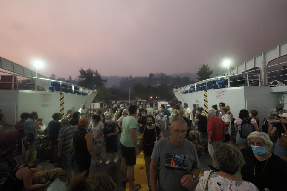People embark a ferry during an evacuation from Kochyli beach as wildfire approaches near Limni village on the island of Evia, about 160 kilometers (100 miles) north of Athens, Greece, Friday, Aug. 6, 2021. Thousands of people fled wildfires burning out of control in Greece and Turkey on Friday, including a major blaze just north of the Greek capital of Athens that claimed one life, as a protracted heat wave left forests tinder-dry and flames threatened populated areas and electricity installations. (AP Photo/Thodoris Nikolaou)