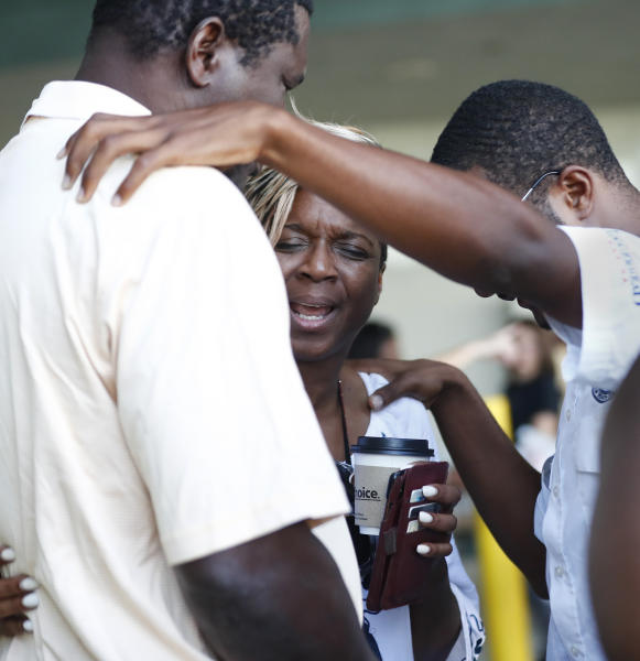 Pastor Linda Collymore, center, praise with Bryce Graham, right and Hurricane Dorian evacuee Arnold Ferguson, left, after arriving on the Grand Celebration cruise ship from Freeport, a city in the Grand Bahamas on Wednesday, Sept. 18, 2019 in Riviera Beach. The cruise ship transported hundreds of evacuees seeking passage from Freeport after the damaged caused by Hurricane Dorian. (AP Photo/Brynn Anderson)