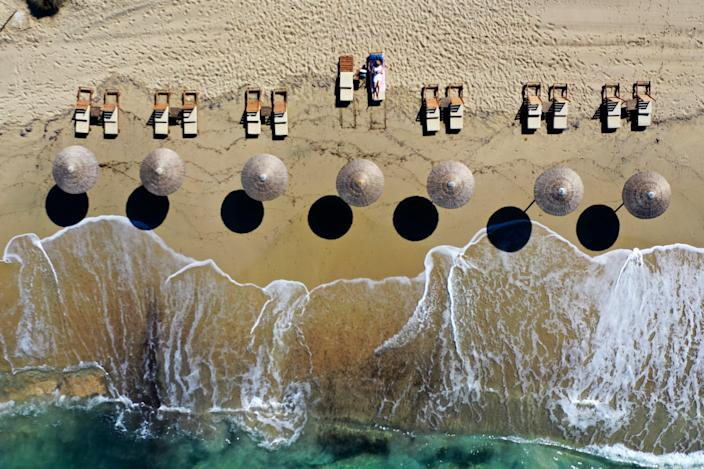 An overhead shot of a beach and water reaching the sand in Greece.