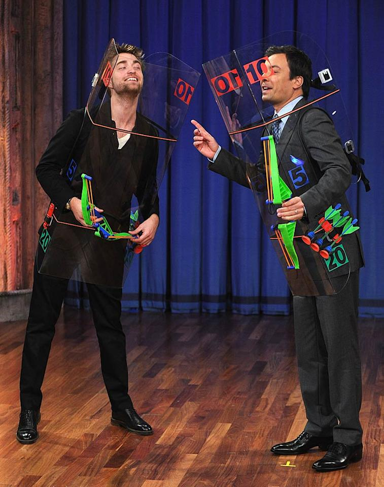 """He may be busy promoting the upcoming """"Twilight"""" flick """"Breaking Dawn - Part 1,"""" but star Robert Pattinson made time to take on Jimmy Fallon in a bizarre game of """"bow and arrow darts,"""" where the targets were each other! RPattz emerged victorious, beating out Jimmy 25 to 10. (11/10/2011)"""