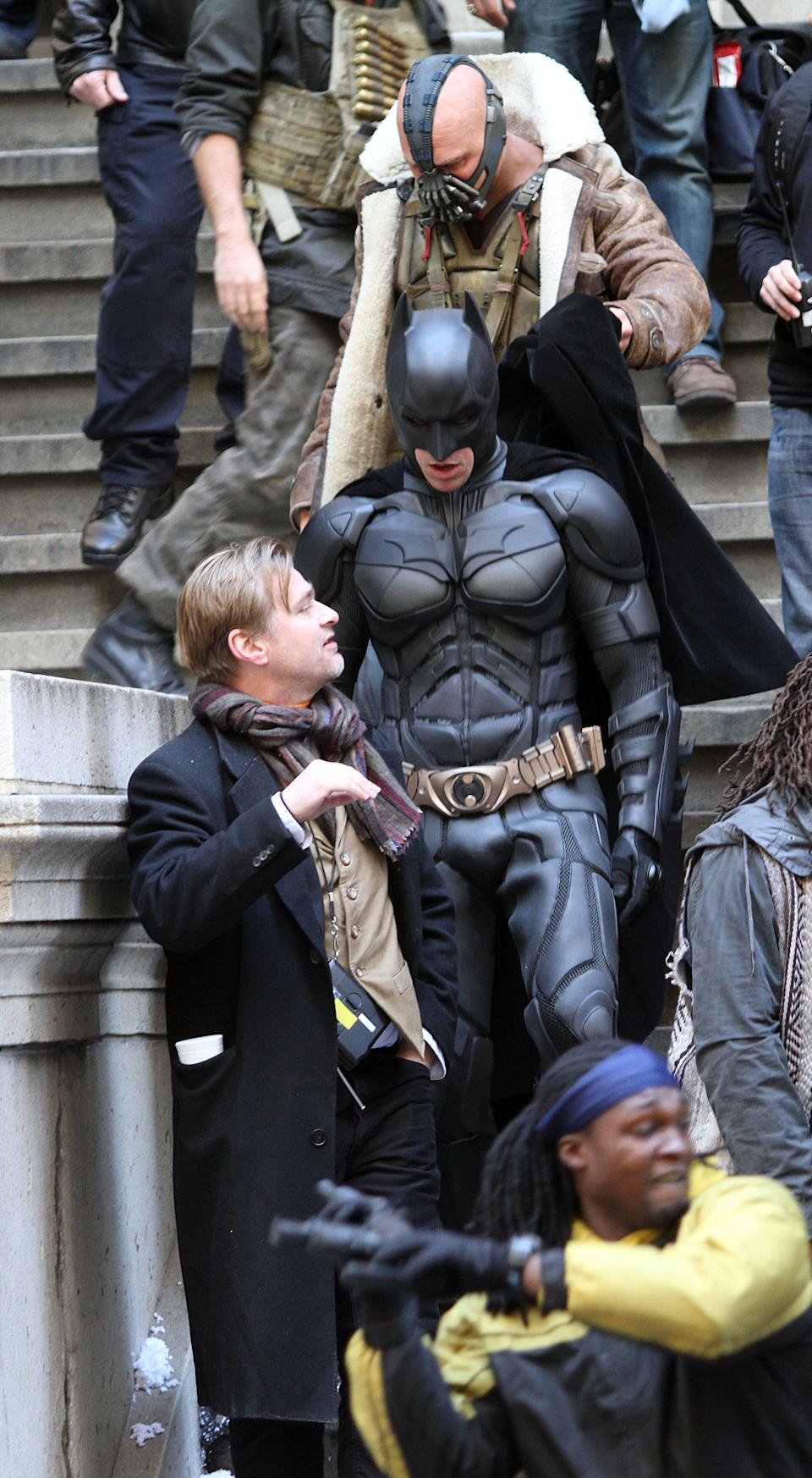 """NEW YORK, NY - NOVEMBER 05:  Actors Christian Bale in costume as Batman, Tom Hardy as Bane  and director Christopher Nolan are seen on the set of """"The Dark Knight Rises"""" on location on Wall Street on November 5, 2011 in New York City.  (Photo by Marcel Thomas/FilmMagic)"""