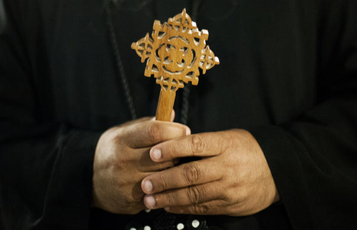 A Coptic Christian monk holds a Coptic cross at Al-Mahraq monastery during the preparation of a religious festival in Assiut, Upper Egypt, Tuesday, Aug. 6, 2013. Islamists may be on the defensive in Cairo, but in Egypt's deep south they still have much sway and audacity: over the past week, they have stepped up a hate campaign against the area's Christians. Blaming the broader Coptic community for the July 3, 2013 coup that removed Islamist President Mohammed Morsi, Islamists have marked Christian homes, stores and churches with crosses and threatening graffiti. (AP Photo/Manu Brabo)