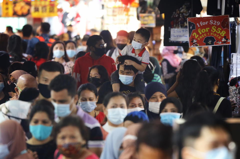 SINGAPORE - JANUARY 10: People wearing protective masks shop on January 10, 2021 in Singapore. As of January 10, the Ministry of Health confirmed 42 new imported COVID-19 cases, with zero cases in the wider community bringing the country's total to 58,907. (Photo by Suhaimi Abdullah/Getty Images)