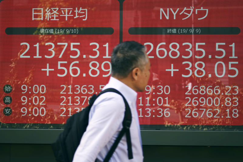 A man walks past an electronic stock board showing Japan's Nikkei 225 index and New York Dow Jones index at a securities firm in Tokyo Tuesday, Sept. 10, 2019. Asian shares were mixed Tuesday after a day of listless trading on Wall Street, as investors awaited signs on global interest rates.(AP Photo/Eugene Hoshiko)
