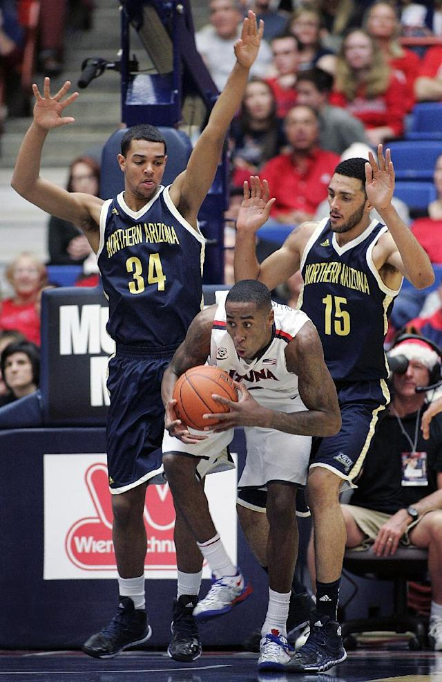 Arizona's Rondae Hollis-Jefferson, center, struggles to keep control of the ball against the defense of Northern Arizona's Jordyn Martin (34) and Len Springs (15) in the second half of an NCAA college basketball game on Monday, Dec. 23, 2013, in Tucson, Ariz. Arizona won 77 - 44. (AP Photo/John MIller)