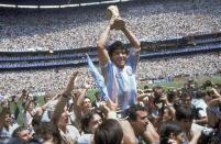 FILE - In this June 29, 1986 file photo, Diego Maradona holds up his team's trophy after Argentina's 3-2 victory over West Germany at the World Cup final soccer match at Atzeca Stadium in Mexico City. The Argentine soccer great who was among the best players ever and who led his country to the 1986 World Cup title before later struggling with cocaine use and obesity, has died. He was 60. (AP Photo/Carlo Fumagalli, File)