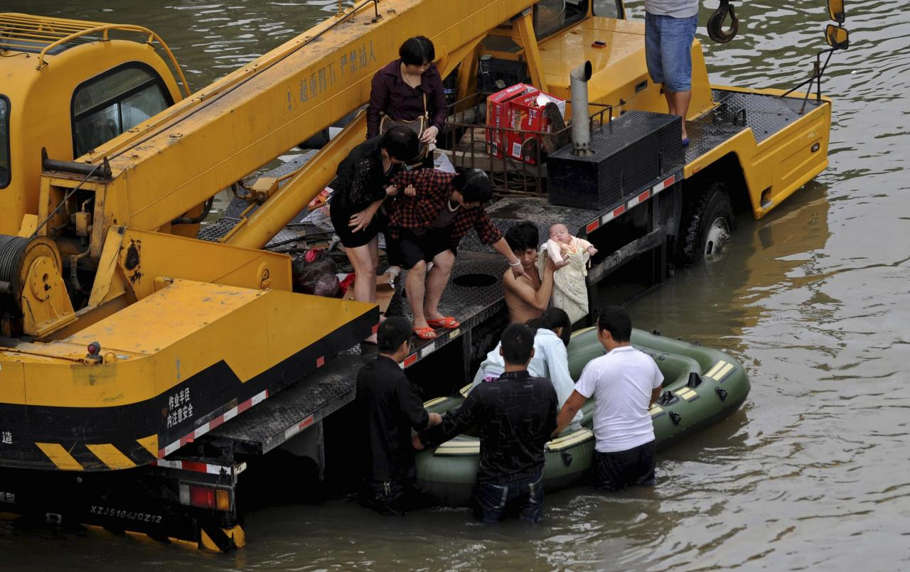 A man holds a baby as they get onto a raft pushed by rescuers on a flooded street after Typhoon Fitow hit Yuyao, Zhejiang province October 9, 2013. Torrential rains caused by Typhoon Fitow continued to lash Shanghai City and Zhejiang Province in eastern China, inundating roads, houses and causing river dike breaches. From Saturday to 10 a.m. Tuesday, Zhejiang saw average precipitation of 201 mm, with 717 mm in worst-hit Yuyao City, Xinhua News Agency reported. REUTERS/Lang Lang (CHINA - Tags: SOCIETY ENVIRONMENT DISASTER)