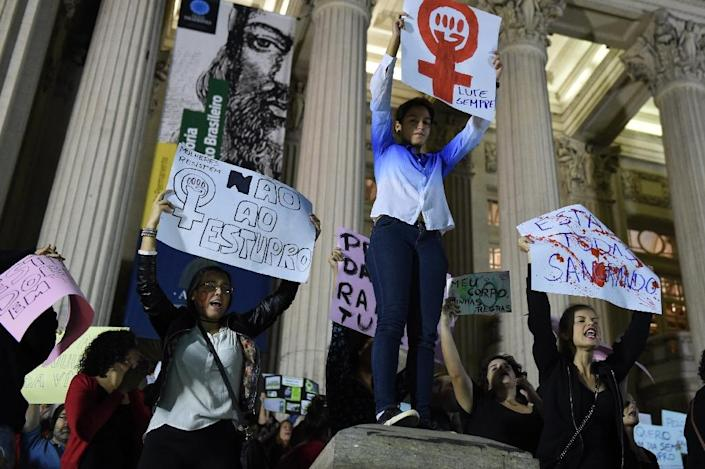 Brazilians protest in front of the Legislative Assembly of Rio de Janeiro (ALERJ) against the gang-rape of a 16-year-old girl (AFP Photo/Vanderlei Almeida)