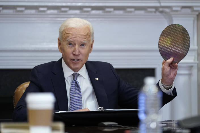 President Joe Biden holds up a silicon wafer as he participates virtually in the CEO Summit on Semiconductor and Supply Chain Resilience in the Roosevelt Room of the White House, Monday, April 12, 2021, in Washington. (AP Photo/Patrick Semansky)