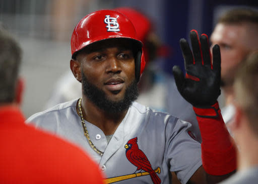 St. Louis Cardinals' Marcell Ozuna is congratulated by teammates after scoring during the eighth inning of a baseball game against the Atlanta Braves, Tuesday, Sept. 18, 2018, in Atlanta. (AP Photo/Todd Kirkland)