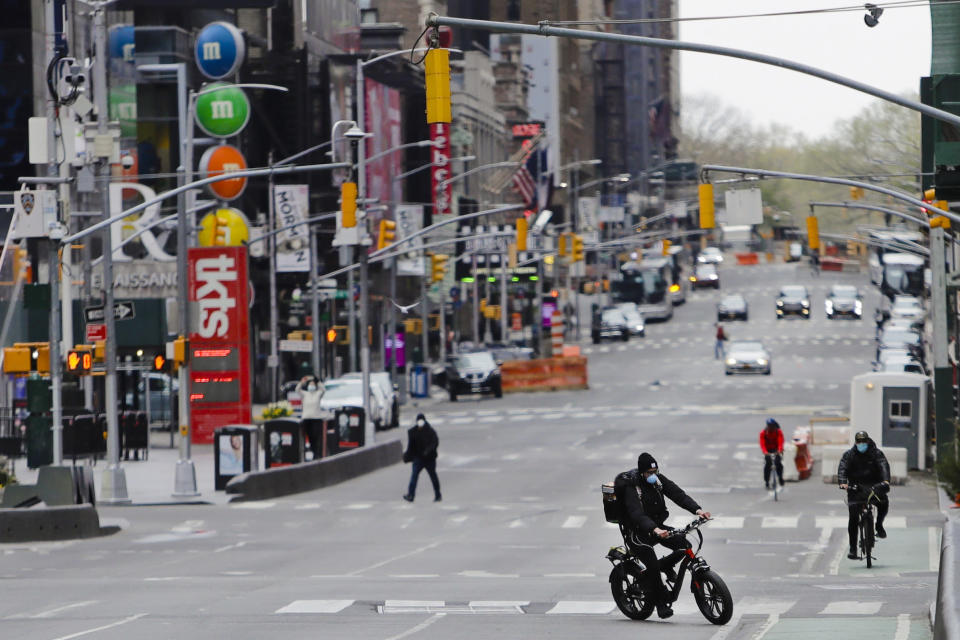 FILE - In this April 17, 2020, file photo, pedestrians and cyclists move through Times Square in New York. New York City streets are largely empty as people continue to stay at home to prevent the spread of COVID-19. (AP Photo/Frank Franklin II, File)