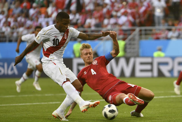 <p>Duelers: Peru's Jefferson Farfan tries to keep the ball under pressure from Simon Kjaer. (AP) </p>