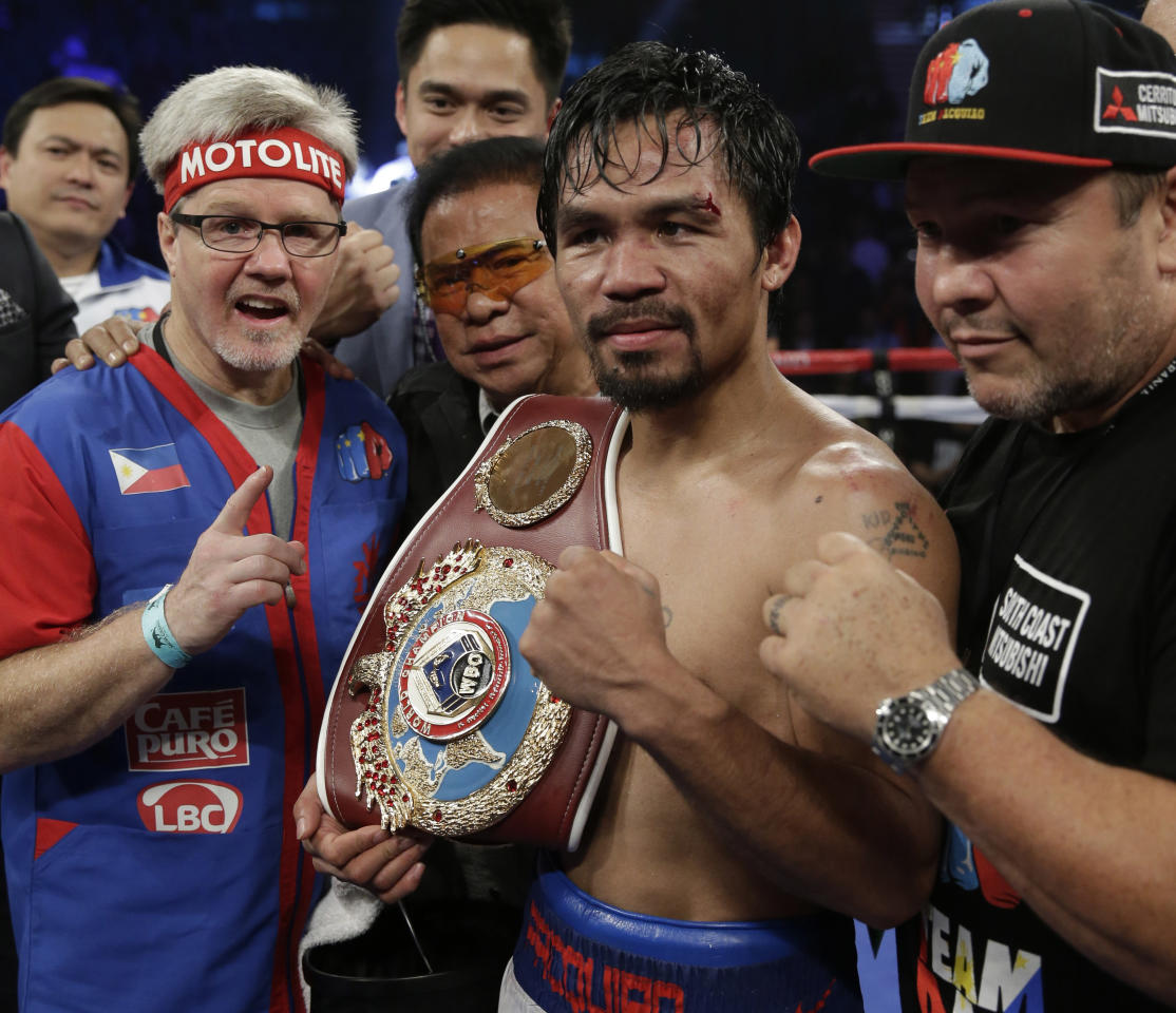 Manny Pacquiao, of the Philippines, center, is joined by trainer Freddie Roach, left, as he poses with the champion's belt following his unanimous decision against Timothy Bradley in their WBO welterweight title boxing fight Saturday, April 12, 2014, in Las Vegas. (AP Photo/Isaac Brekken)