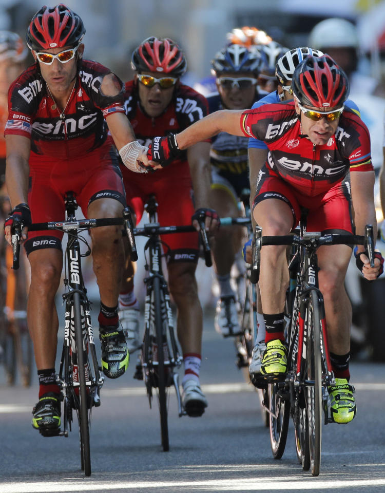 Cadel Evans of Australia, left, thanks teammate George Hincapie of The US, left, when crossing the finish line of the 16th stage of the Tour de France cycling race over 197 kilometers (122.4 miles) with start in Pau and finish in Bagneres-de-Luchon, France, Wednesday July 18, 2012. (AP Photo/Laurent Rebours)