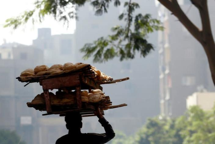 FILE PHOTO: A bakery worker carries fresh bread in Cairo