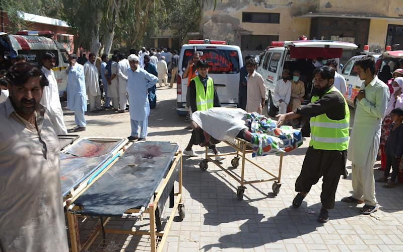 Pakistani volunteers transport the body of a victim murdered at a Sufi shrine  - Credit: AFP