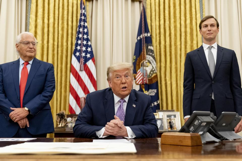 President Donald Trump, center, accompanied by U.S. Ambassador to Israel David Friedman, left, and Trump's White House senior adviser Jared Kushner, right, speaks in the Oval Office at the White House, Wednesday, Aug. 12, 2020, in Washington. Trump said on Thursday that the United Arab Emirates and Israel have agreed to establish full diplomatic ties as part of a deal to halt the annexation of occupied land sought by the Palestinians for their future state. (AP Photo/Andrew Harnik)