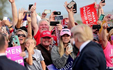 FILE PHOTO: Supporters applaud U.S. President Donald Trump as he arrives to attend a campaign rally at Middle Georgia Regional Airport in Macon
