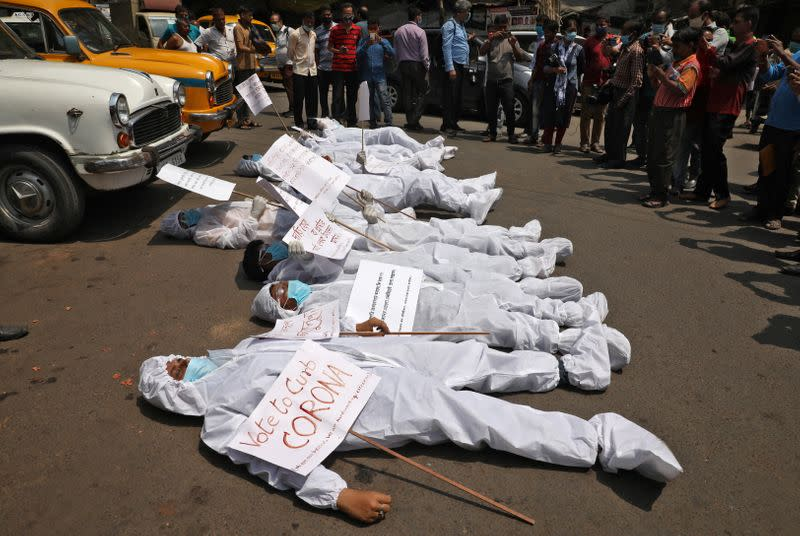 Demonstrators in protective suits and masks lie on a road during a protest demanding to stop election and campaign rallies in the eastern state of West Bengal, in Kolkata