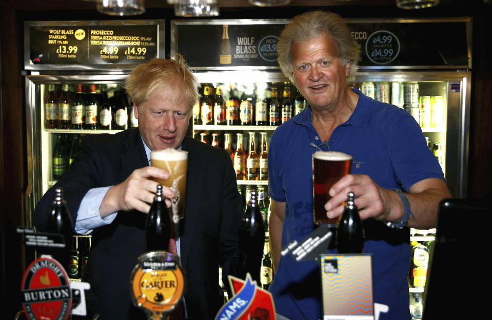Conservative Party leadership candidate Boris Johnson, left, gestures with Tim Martin, Chairman of JD Wetherspoon, during a visit to Wetherspoons Metropolitan Bar in London, Wednesday July 10, 2019. (Henry Nicholls/Pool Photo via AP)