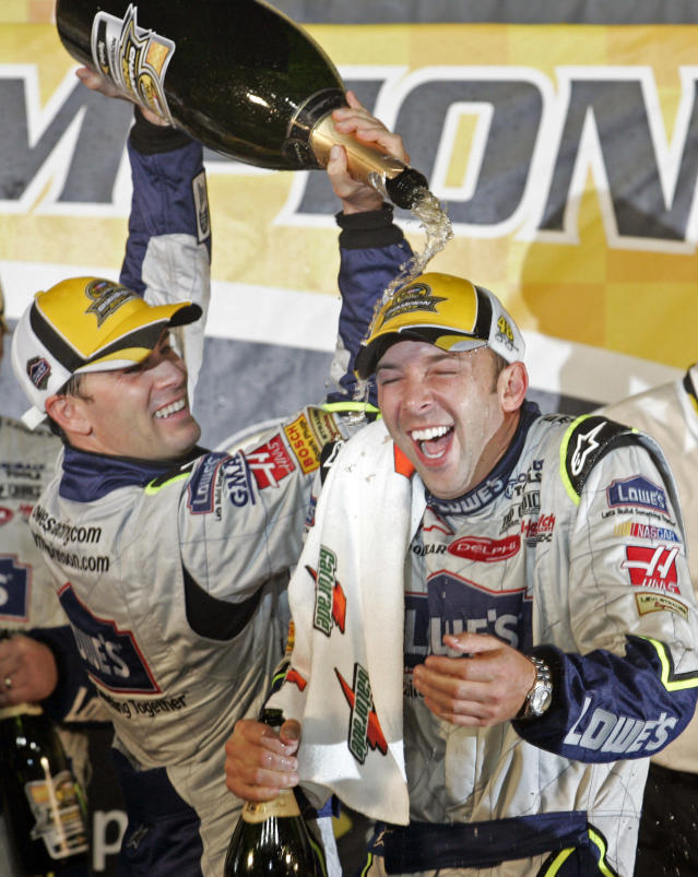 FILE - In this Nov. 18, 2007, file photo, Jimmie Johnson, left, pours champagne on crew chief Chad Knaus as they celebrate after winning the NASCAR Nextel Cup Series championship in Homestead, Fla. There will be no eighth NASCAR title for Johnson and Knaus. Hendrick Motorsports will split the driver and crew chief at the end of this season, the team announced Wednesday, Oct. 10, 2018. (AP Photo/Terry Renna, File)