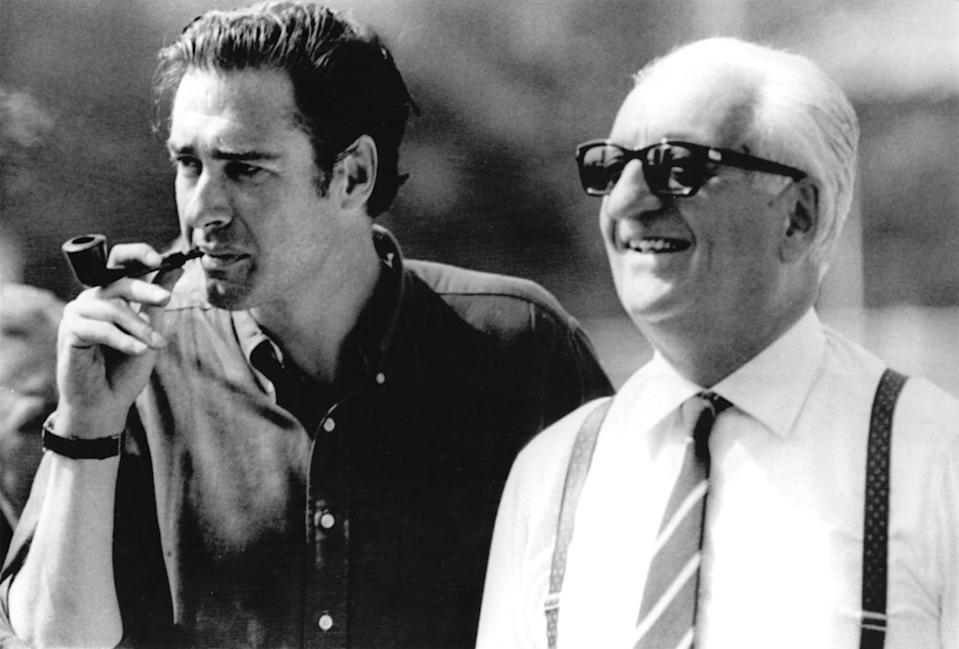 """Movie director John Frankenheimer, left, and Enzo Ferrari, right, owner of Italian car factory pictured at Monza autodrome during a pause of """"Grand Prix"""" shooting, August 23, 1966. (AP-PHOTO/Armando Trovati)"""