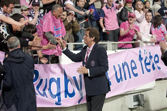 Stade Francais' president Max Guazzini (C) acknowledges the audience after winning the European Challenge Cup semi final rugby union match Stade Francais vs. Clermont at the Charlety stadium in Paris on April 29, 2011. AFP PHOTO / BERTRAND LANGLOIS (Photo credit should read BERTRAND LANGLOIS/AFP/Getty Images)