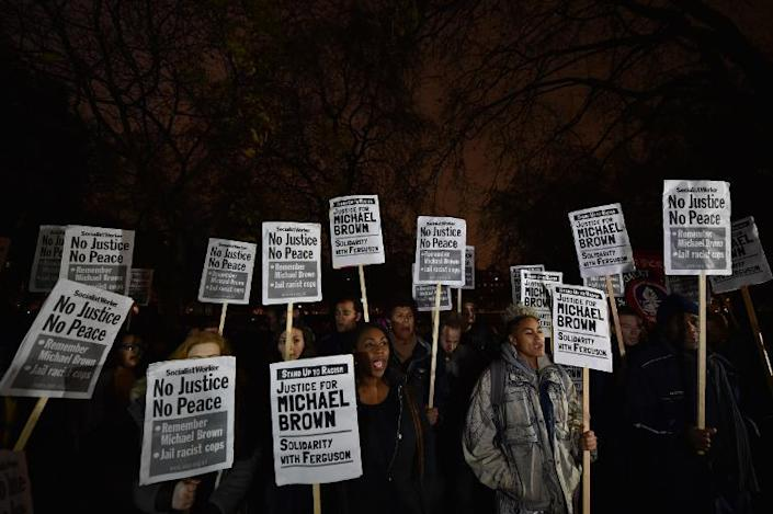 Demonstrators stand and chant with placards during a protest outside the US embassy in London on November 26, 2014 over the US court decision not to charge the policeman who killed unarmed black teenager Michael Brown in the town of Ferguson (AFP Photo/Leon Neal)