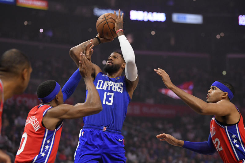 Los Angeles Clippers guard Paul George, center, shoots as Philadelphia 76ers guard Josh Richardson, left, and forward Tobias Harris defend during the first half of an NBA basketball game Sunday, March 1, 2020, in Los Angeles. (AP Photo/Mark J. Terrill)