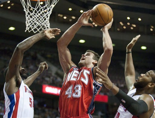 New Jersey Nets' Kris Humphries (43) goes to the basket between Detroit Pistons' Jason Maxiell, left, and Greg Monroe, right, in the first half of an NBA basketball game Friday, Feb. 10, 2012, in Auburn Hills, Mich. (AP Photo/Duane Burleson)