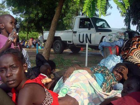 A U.N. truck drives past displaced South Sudanese families resting in a camp for internally displaced people in the UNMISS compound in Tomping, Juba, South Sudan