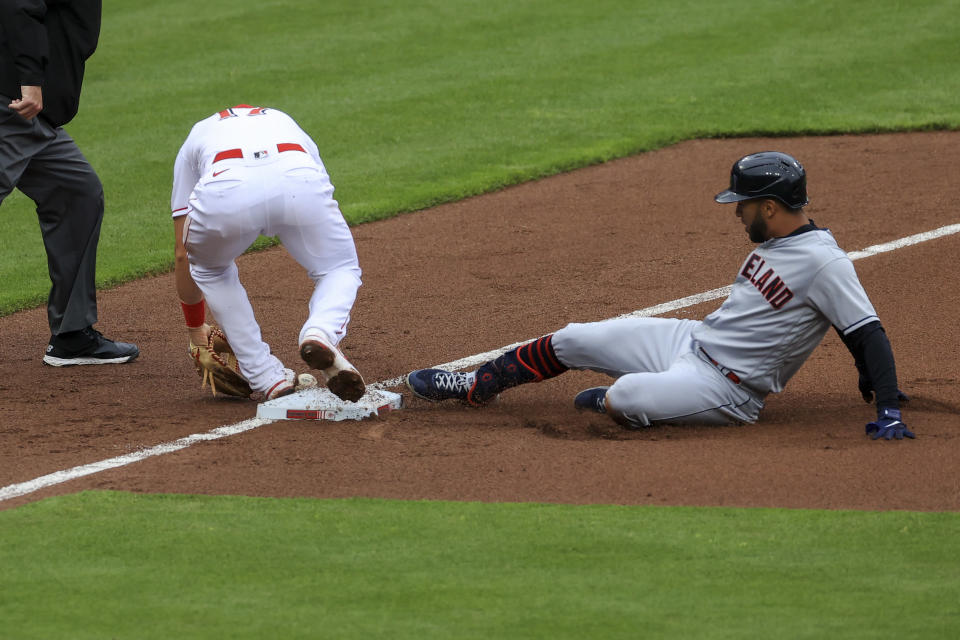 Cincinnati Reds' Kyle Farmer, second from right, attempts to field the ball as Cleveland Indians' Eddie Rosario, right, slides safely into third base after hitting an RBI-triple during the third inning of a baseball game in Cincinnati, Saturday, April 17, 2021. (AP Photo/Aaron Doster)