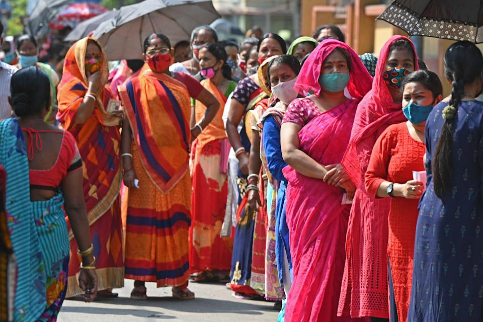 Voters stand in a queue at a polling station to cast their ballot during the 5th phase of West Bengal's state legislative assembly elections in Kolkata on April 17, 2021. (Photo by Dibyangshu SARKAR / AFP) (Photo by DIBYANGSHU SARKAR/AFP via Getty Images)