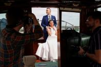 Tokacs-Mathe and Aszalos pose during their wedding photoshoot on a water limousine on the Danube river as the coronavirus disease (COVID-19) restrictions are eased in Budapest